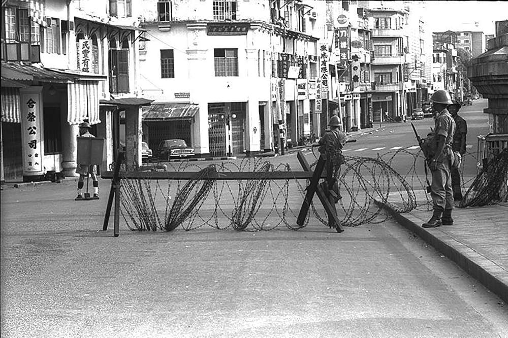 Police officers and soldiers on  guard at Bras Basah Road in  July 1964, after an outbreak of  communal rioting. Singapore's  commitment to strengthening  the ties between our many  communities is based on the  painful lessons of the past.