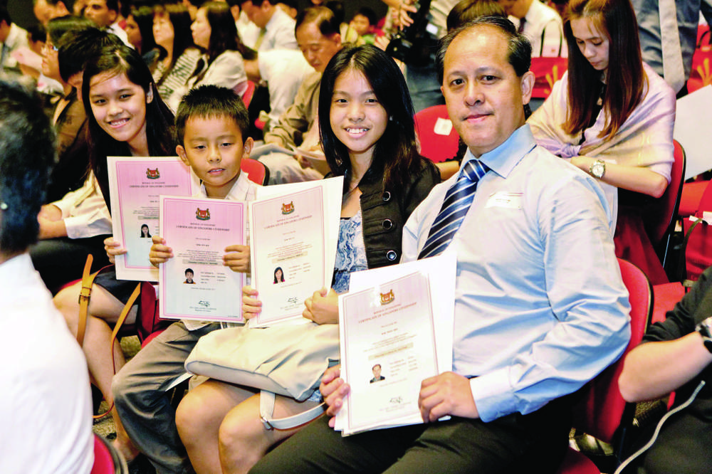 New citizens with their  citizenship certificates at the National Citizenship Ceremony