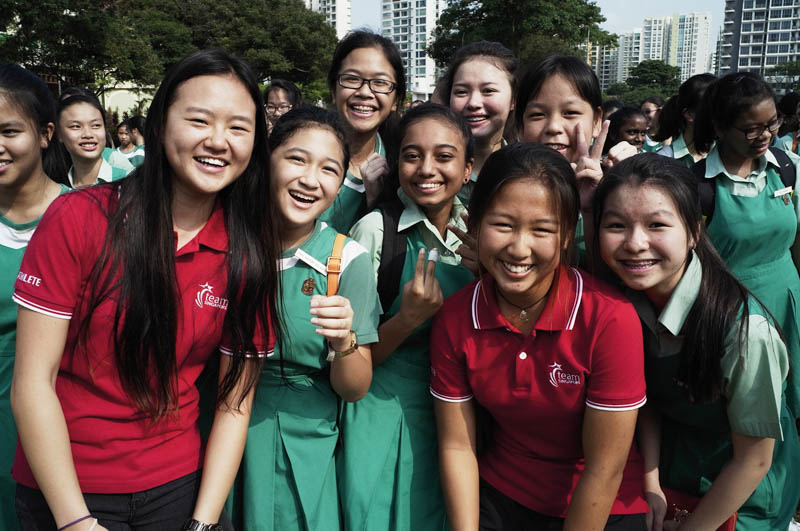 "National sailors Savannah Siew (left) and Kimberly Lim with TKGS students during the ""50 Waves of Cheer"" roadshow in October 2014."