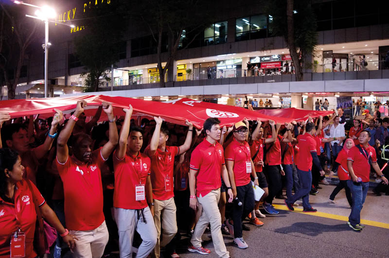 Athletes and officials carried the Team Singapore flag down Orchard Road at the three-month countdown ceremony in March 2015.